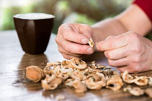 Hands of unrecognizable woman cracking walnuts, wooden table