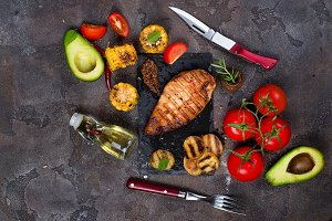 Marinated grilled healthy chicken breasts cooked on BBQ and served with fresh tomato, avocado, potatoes and corn