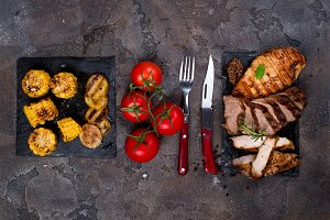 Fresh three types of grilled steak (chicken, pork, beef) on slate plate with herbs, corn, tomato and grilled potatoes