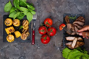 female hand holds a fork with slice tomato on the background fresh three types of grilled steak on slate plate with spinach, tomato and grilled potatoes