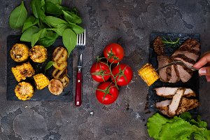 female hand holds a fork with grilled corn on the background fresh three types of grilled steak on slate plate with spinach, tomato and grilled potatoes