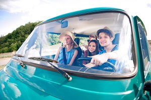 Hipster boy driving an old campervan with teenagers, roadtrip