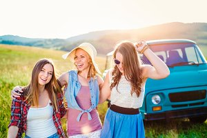 Three teenage hipster girls on a roadtrip, summer day