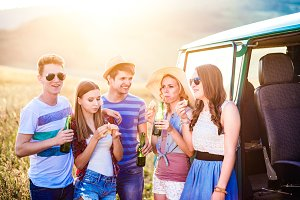 Group of teenage hipsters on roadtrip, drinking beer, eating