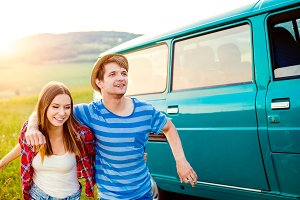 Teenage couple in love outside in nature, green campervan