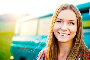 Teenage girl smiling against green campervan outside in nature