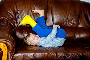 Boy with broken leg in cast lying on couch.