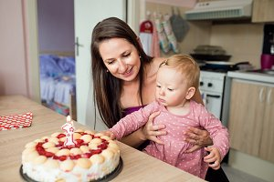 Mother holding her baby daughter with birthday cake