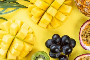 Fresh tropical fruits on yellow
