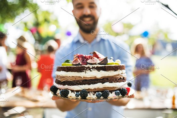 Man With A Cake On A Family Celebration Or A Garden Party Outside