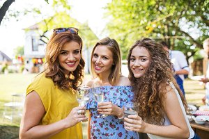 Portrait of three women on a family celebration or a barbecue party outside in the backyard.