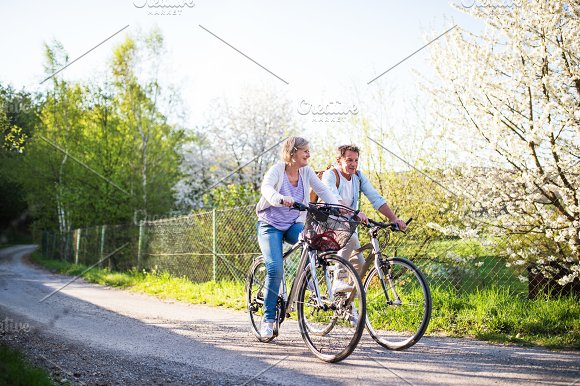 Senior Couple With Bicycles Outside In Spring Nature