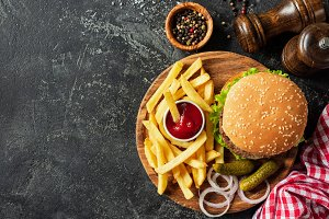 Burger and fries on wooden board