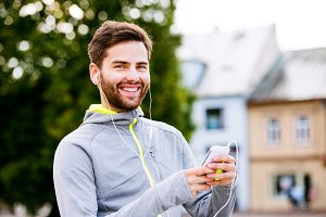 Young hipster runner in town with smartphone