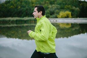 Man in yellow neon jacket runnig at the lake