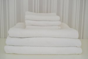 A pile of white fluffy towels in the closet. Service in the hotel concept. laundry