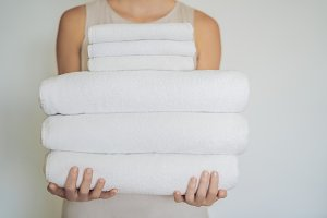 A woman is holding a stack of white towels. Concept of service in hotels, laundry, spa