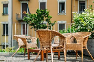 Wooden table and chairs on an outdoor terrace in a residential neighbourhood during the summer.