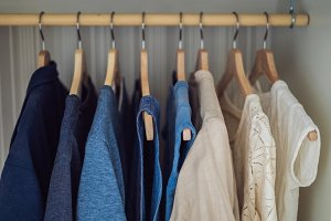 Clothes on hangers in the cabinet gradient from white to dark blue