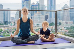 Mom and son are practicing yoga on the balcony in the background of a big city. Sports mom with kid doing morning work-out at home. Mum and child do the exercises together, healthy family lifestyle concept