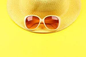 Hat, sunglasses on a pastel yellow background.