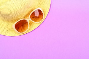Hat, sunglasses on a pastel pink, purple background.