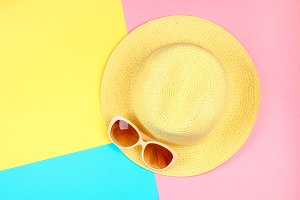 Hat, sunglasses on a three-color pastel background of blue, yellow and pink.
