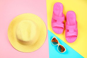 Hat, sunglasses and slippers on a three-color pastel background of blue, yellow and pink.