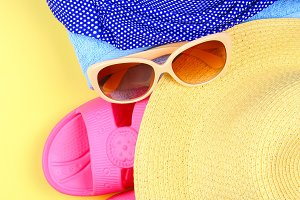 Slippers, swimsuit bikini, towel, hat and sunglasses on a pastel yellow background. Travel, sea, vacation, holiday.