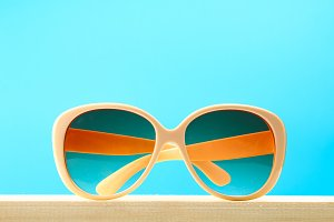Yellow sunglasses on a wooden shelf on a blue pastel background. Minimalism.