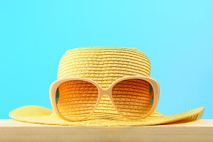Yellow sunglasses and hat on a wooden shelf on a blue pastel background. Minimalism.
