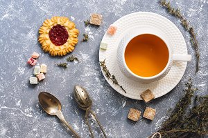 Herbal tea with thyme with sweets on a gray background, top view. Flat lay