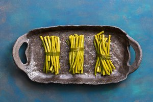 Green string beans. Green beans on a ceramic dish, blue background. The view from above, flat lay.