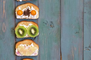 A set of sandwiches with a variety of filling in a row on a green rustic wooden background. Sweet sandwiches with cream and fruit fillings. Top view, copy space.