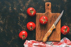 Fresh tomatoes on a dark background, cutting board, checkered napkin, knife. Top view, copy space. Toned photo.
