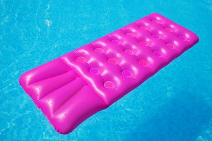 Pink air mattress on a swimming pool tropical
