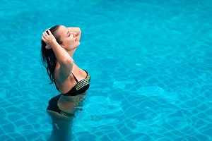 young brunette woman sunbathe swimming pool