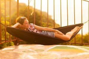 Young slim woman in tropical exotic hammock