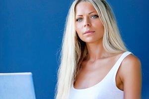blonde woman freelancer drinks coffee works online