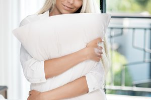 blonde slim woman long hair hug pillow in bed