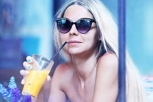 blonde woman with long hair drinks juice in cafe