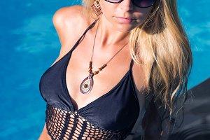 slim blonde woman gets suntan near swimming pool