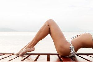 young slim woman legs gets suntan near sea