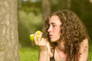woman eating apple on a green field