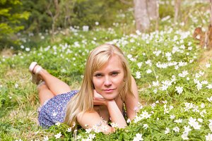 Pretty blonde woman on a spring meadow in flowers