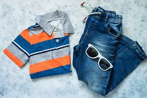 Child clothes - jeans, polo and sunglasses top view.