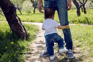 baby boy standing at his father's feet in a green garden