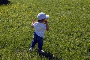 a child in a white cap runs