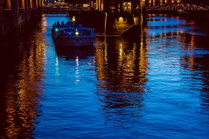 Water castle in old Speicherstadt or Warehouse district, tourist boat on a channel. Hamburg, Germany