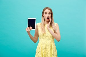 Portrait of a surprised amazed young woman looking at digital tablet isolated on a blue studio background.